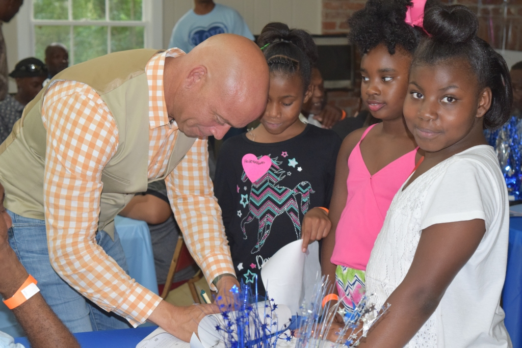 Mayor Grennell signs posters for the kids